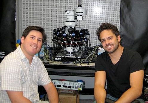 Joint first authors of the paper Rodrigo Perin (on the left) and Costas Anastassiou (on the right) in front of the electrophysiological instrument used for the experiments.