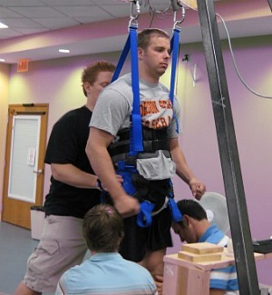 Rob Summers, 25, in the harness that provides support while he receives electrical stimulation to his spinal cord. The experimental procedure has allowed Summers to stand and move his legs voluntarily. [Credit: Rob Summers]