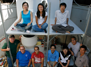 The Caltech team (top left to right - Hao Zhang, Yan Qu, Daejung Kwon - bottom middle from left to right - Clement Cid, Asghar Aryanfar, and Kangwoo Cho, along with members of the Caltech facilities team) in front of the toilet system, which includes a Western-style toilet, a urinal, and a squat toilet.