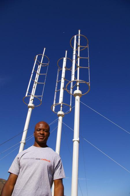 John Dabiri with three of the vertical-axis wind turbines (VAWTs) at his experimental wind farm in Northern Los Angeles County.
